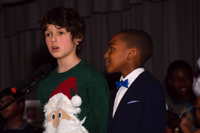 amos in santa jumber and romaine in suit singing