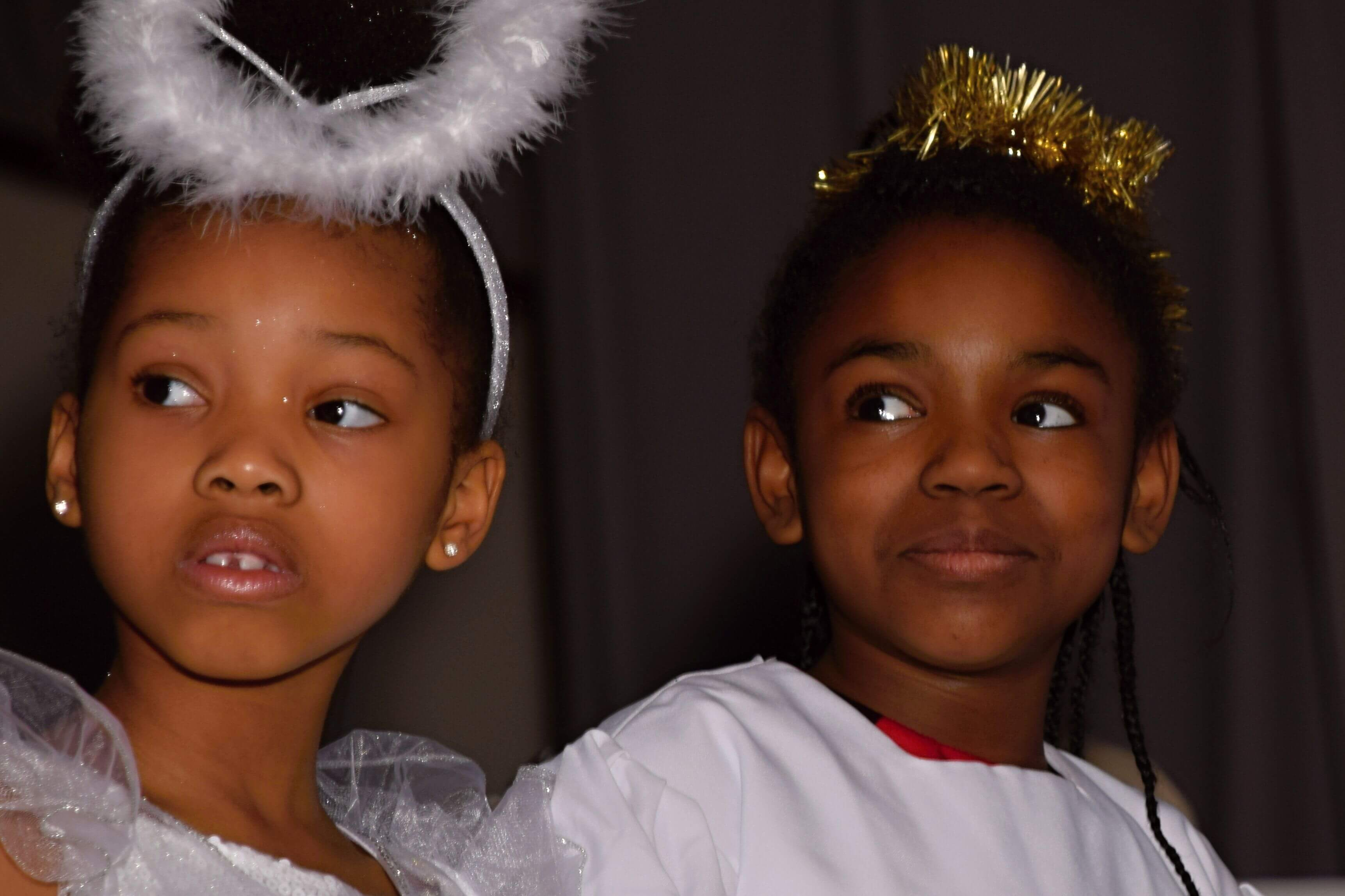 two girls playing angles in nativity story play