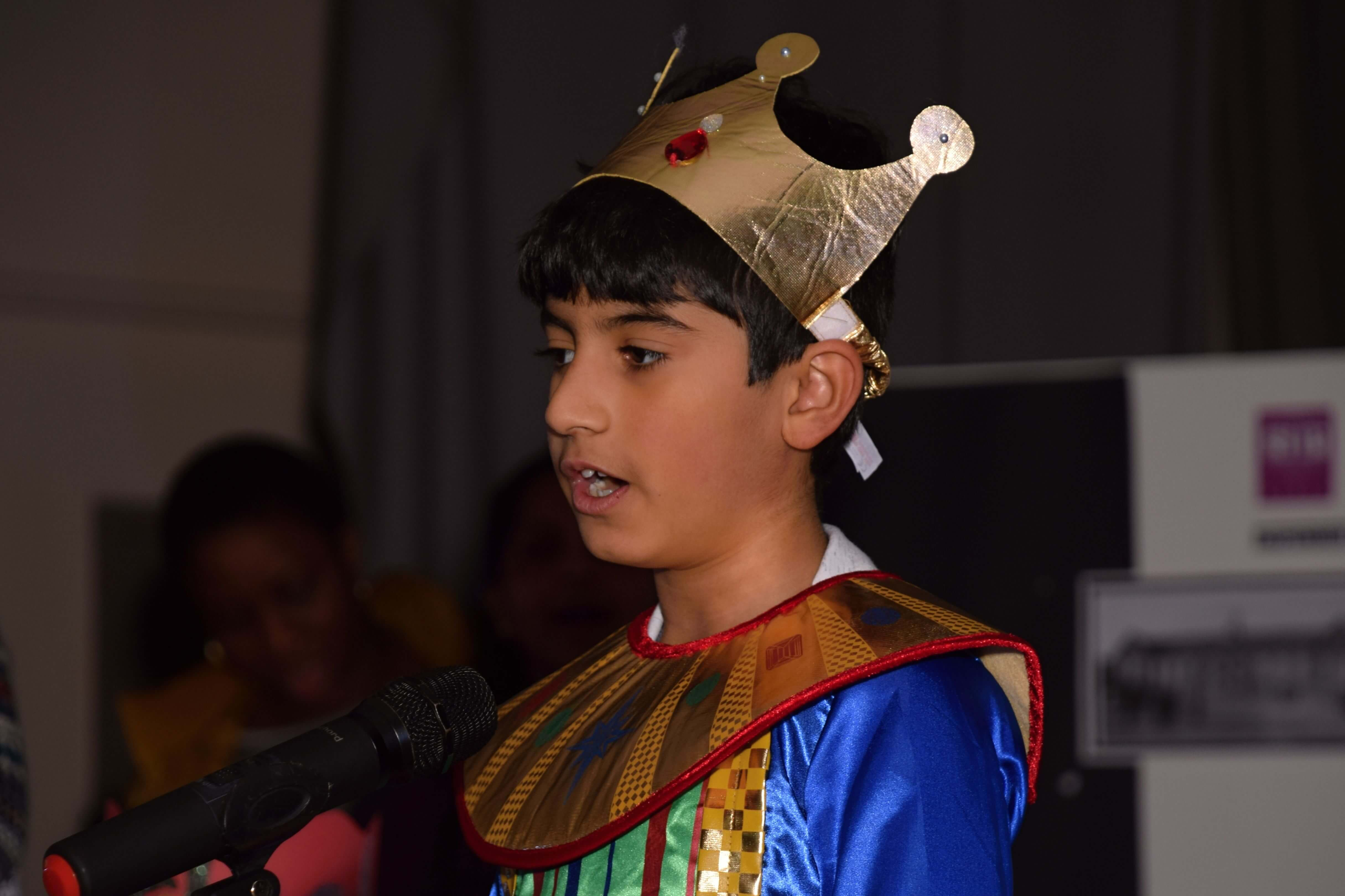 boy playing a king behind microphone