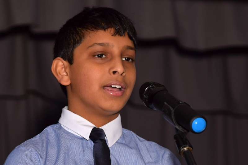 boy with tie singing into a microphone
