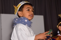 boy dressed as a magi with crown holding a present