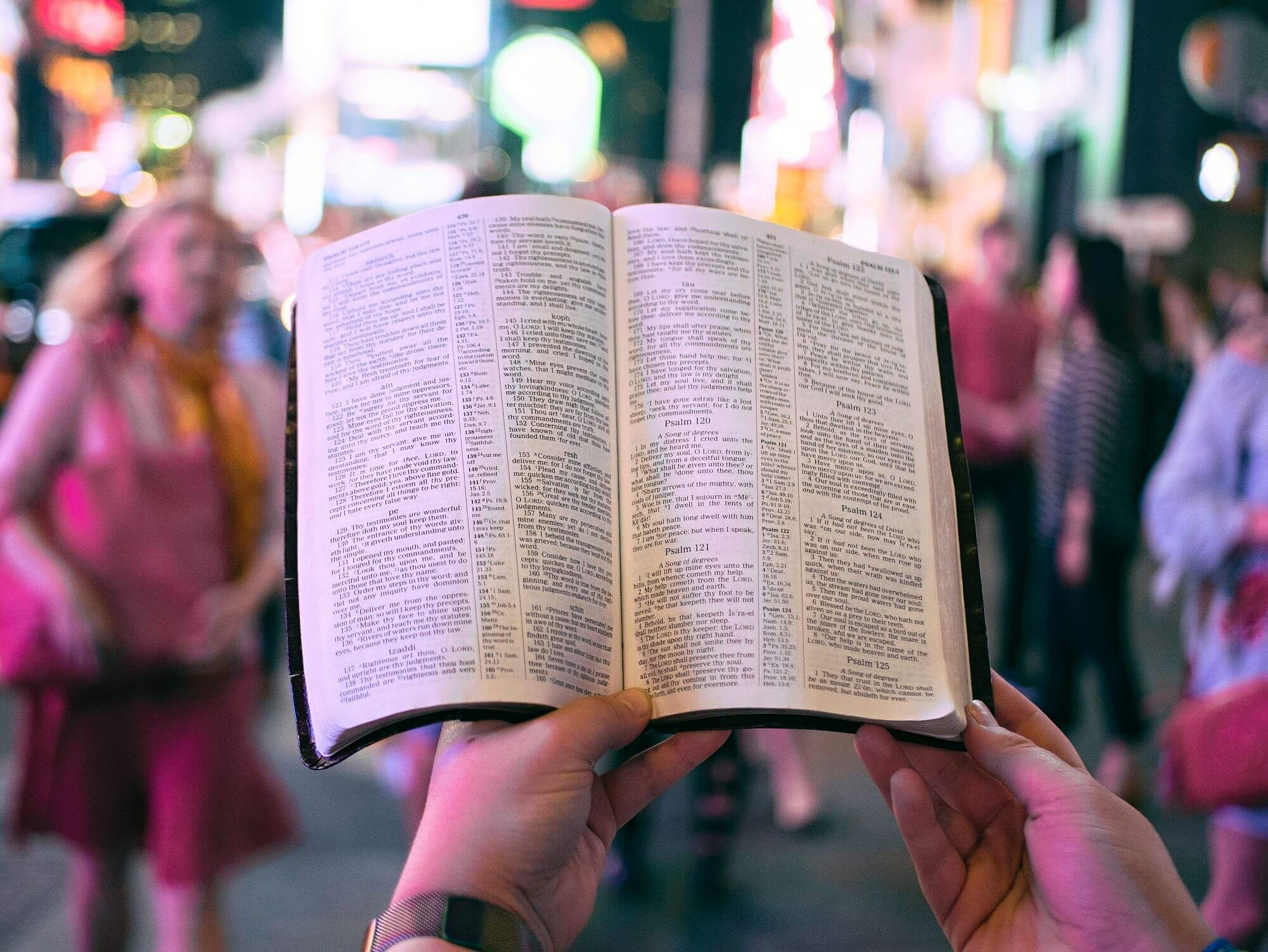 open bible walking through crowd