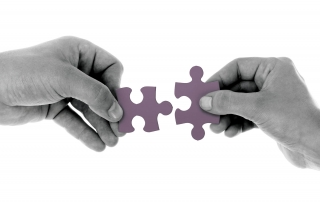two hands matching jigsaw puzzle pieces