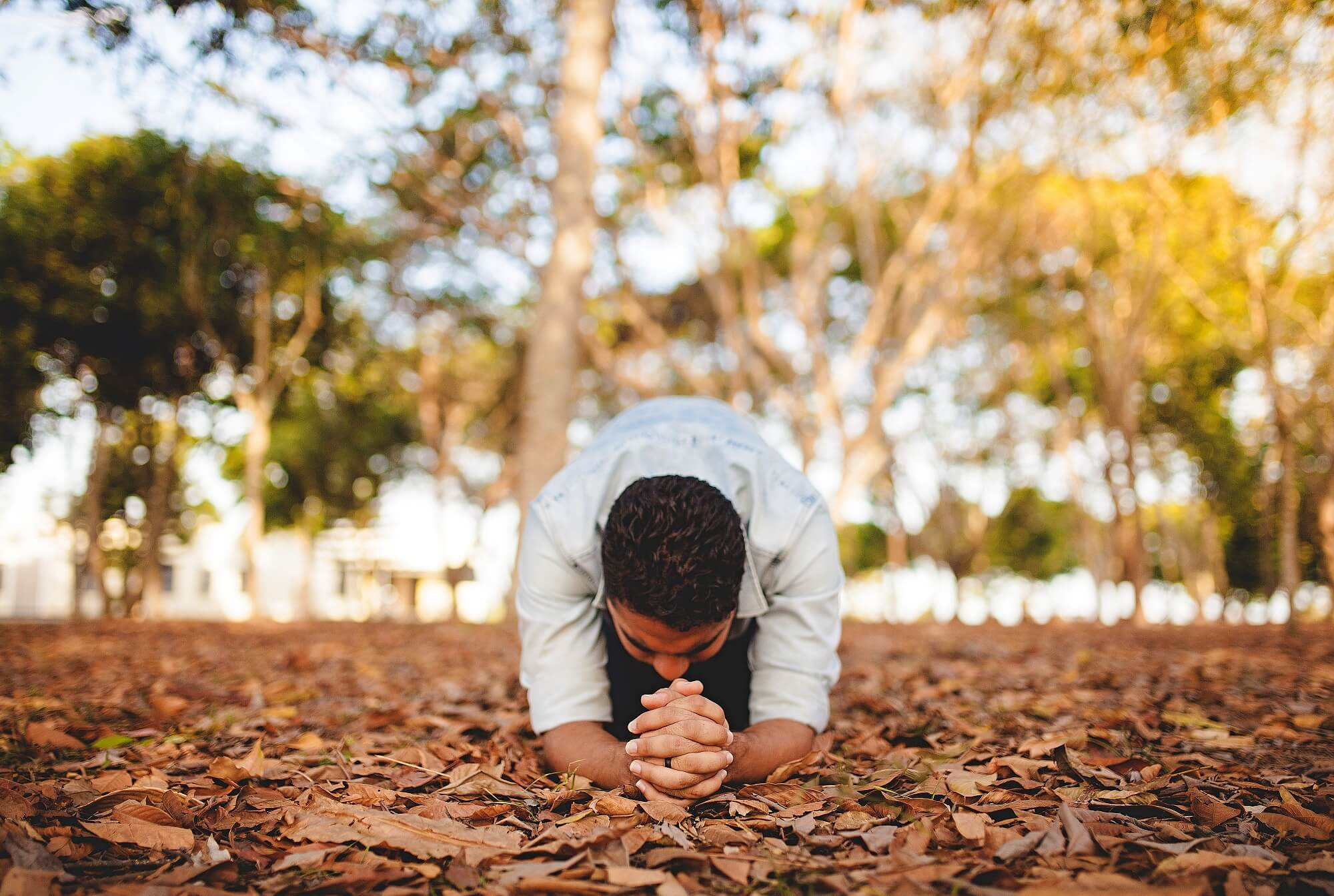 praying man folding hands on the ground