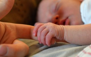 infant/baby holding finger of adult