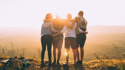 friends embracing looking at sunset