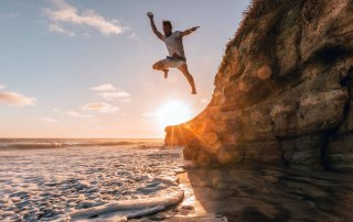 man jumping off a cliff sunrise