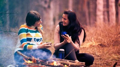 two women talking at campfire