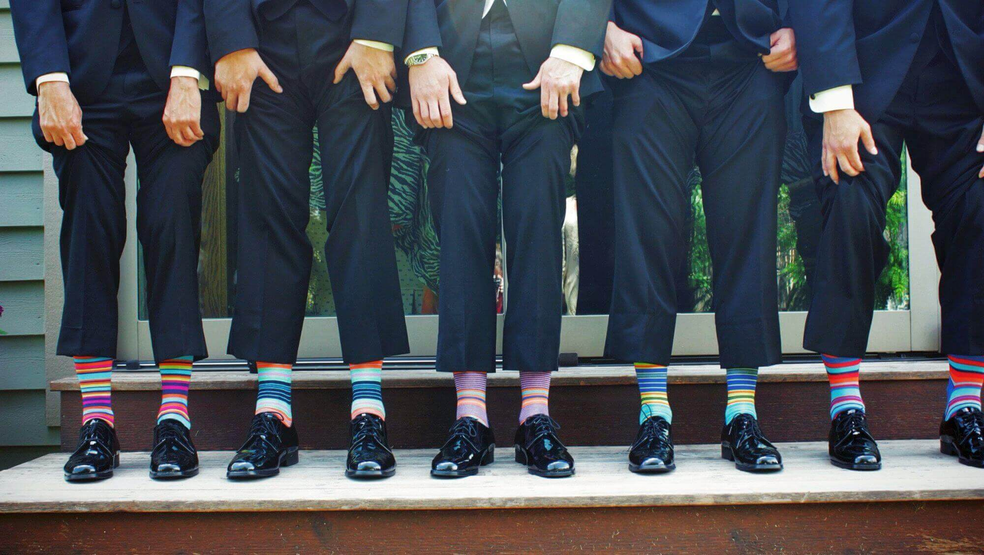 men lifting their pants showing colorful socks