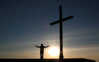 woman lifting arms next to a cross