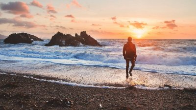 man walking into the sea at sunset wearing shoes