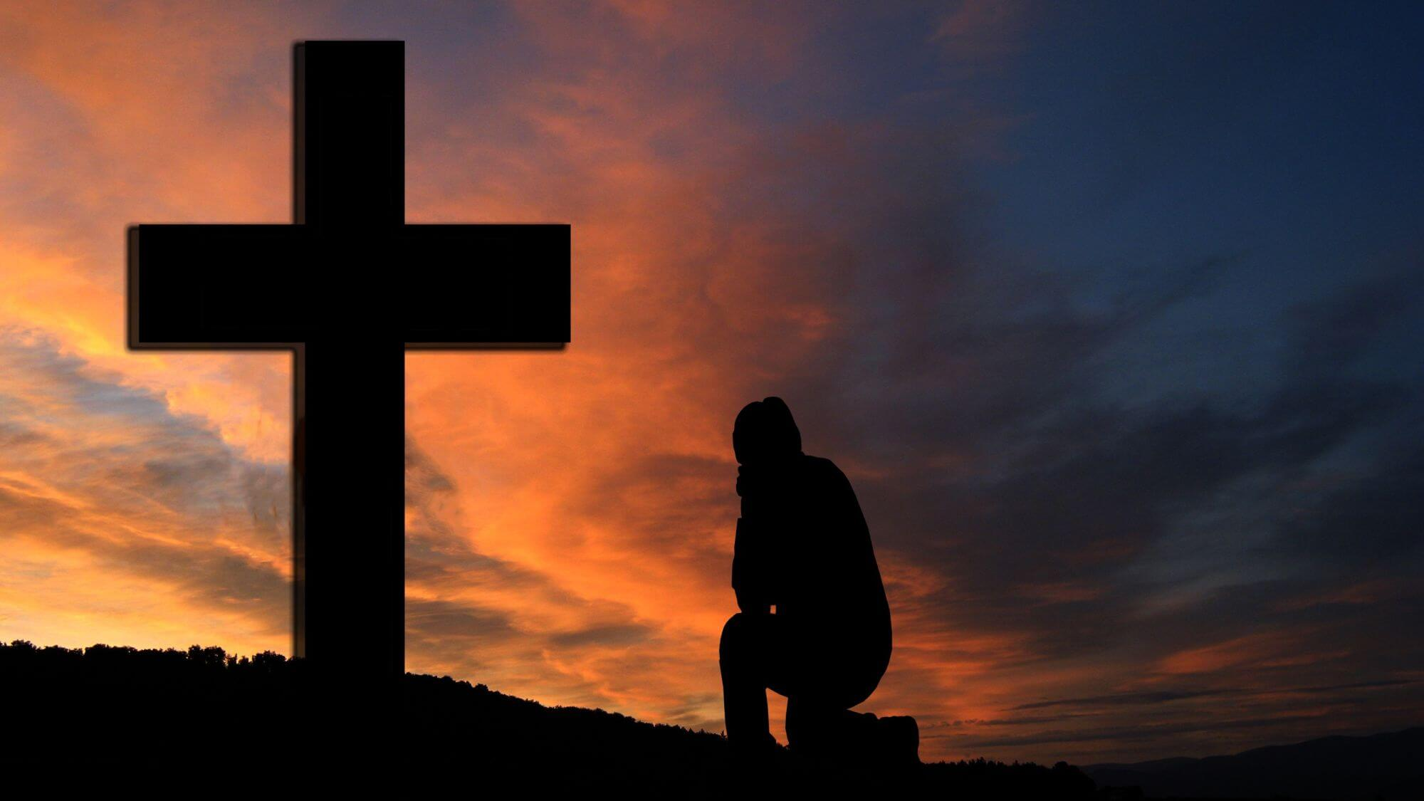 person kneeling before the cross of Jesus